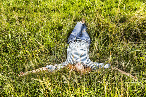 Young woman relaxing on a meadow - FMKF04447