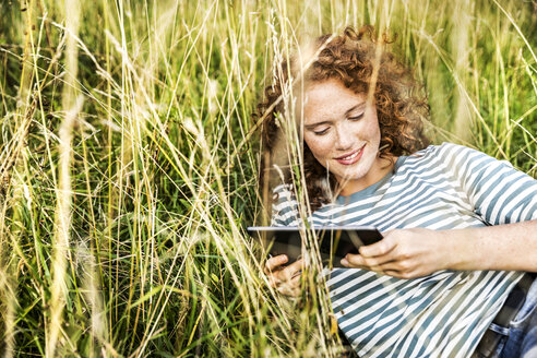 Smiling young woman relaxing on a meadow with tablet - FMKF04453
