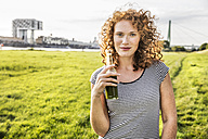 Germany, Cologne, portrait of redheaded young woman with beverage - FMKF04456