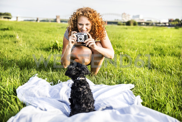 Germany, Cologne, portrait of smiling young woman on meadow taking picture of her dog - FMKF04465