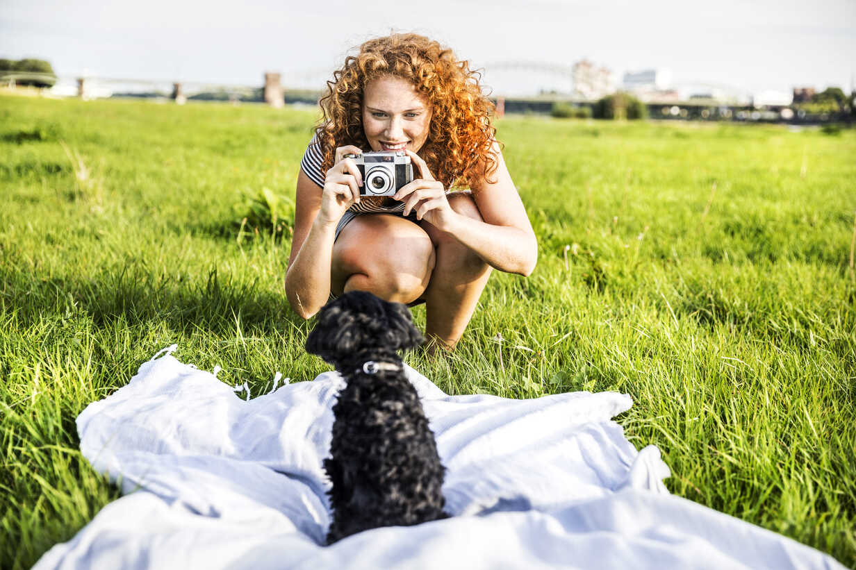 Germany, Cologne, portrait of smiling young woman on meadow taking picture of her dog - FMKF04465 - Jo Kirchherr/Westend61