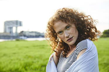 Germany, Cologne, portrait of redheaded freckled young woman - FMKF04471