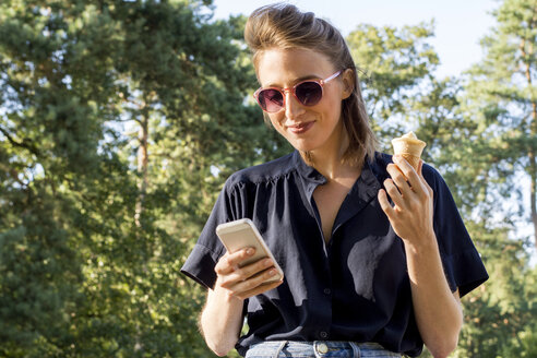 Young woman with ice cone using smartphone - LMF00751
