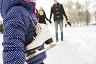 Little girl going ice skating with her parents - HAPF02099
