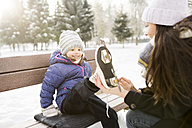 Mother helping daughter to put on her ice skates - HAPF02102