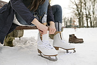 Woman putting on her ice skates - HAPF02111