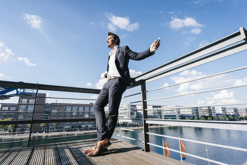 Happy businessman standing on balcony, with arms out - KNSF02720