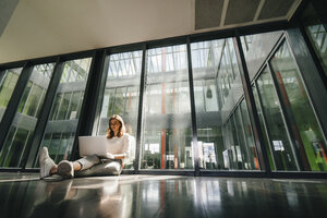Businesswoman sitting on ground in empty office, using laptop - KNSF02732