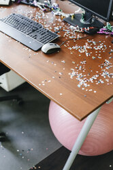 Desk with confetti and streamers on computer after a birthday party - KNSF02741