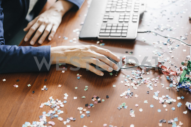 Hand of a woman working on a desk full of confetti - KNSF02750