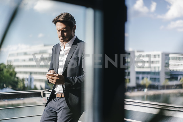 Businessman standing on balcony, holding smartphone - KNSF02774