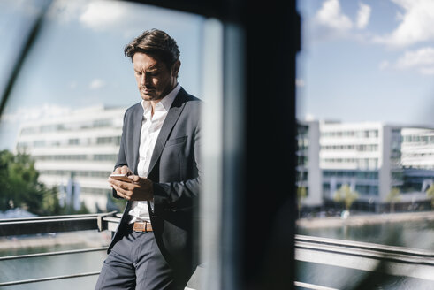 Businessman standing on balcony, holding smartphone - KNSF02774
