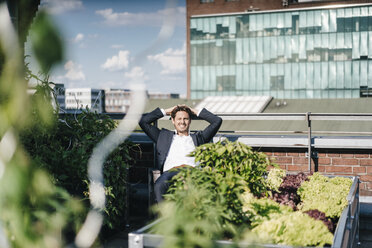 Businessman relaxing in his urban rooftop garden - KNSF02783