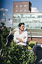 Businessman cultivating plants in his urban rooftop garden - KNSF02786