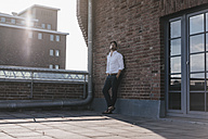 Businessman standing on rooftop terrace, with hands in pockets - KNSF02789