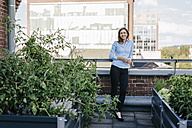 Businesswoman standing on her urban rooftop garden - KNSF02795