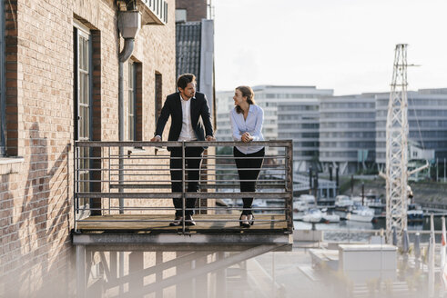 Business people standing on balcony, discussing - KNSF02807