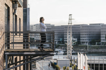 Businesswoman standing on a balcony, with eyes closed - KNSF02810