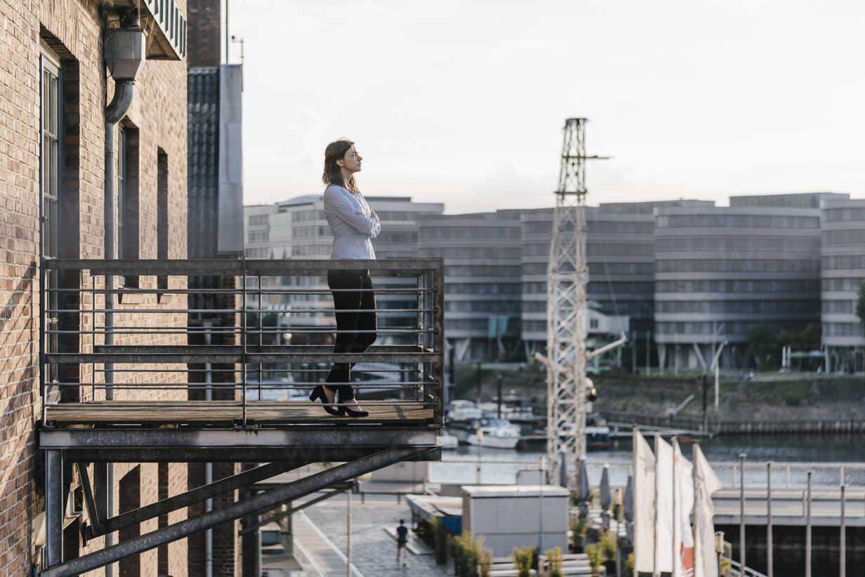 Businesswoman standing on a balcony, with eyes closed - KNSF02810 - Kniel Synnatzschke/Westend61