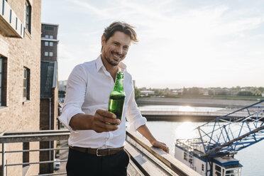 Happy businessman standing on balcony, drinking beer - KNSF02816