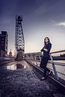 Businesswoman standing at wet inner harbor, thinking - KNSF02819