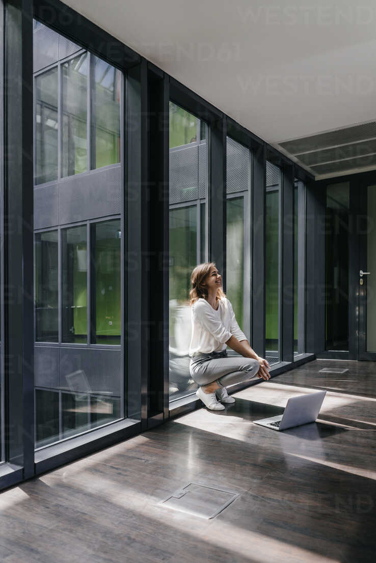 Happy businesswoman crouching on floor - KNSF02828 - Kniel Synnatzschke/Westend61