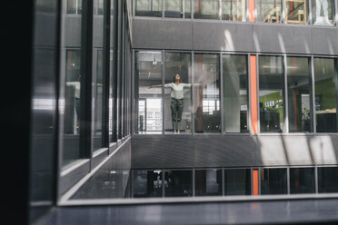 Woman standing at office window, with arms outstretched - KNSF02837