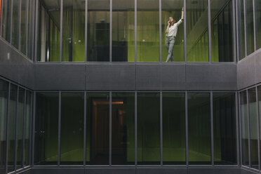 Woman standing at office window, making a phone call - KNSF02840