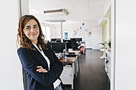 Confident businesswoman standing smiling in office - KNSF02843