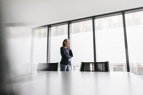 Successful businesswoman standing in board room - KNSF02846