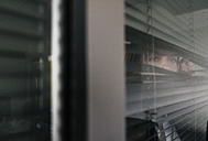 Woman standing by window, spying through blinds - KNSF02852