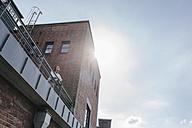 Businesswoman standing on terrace of industrial building - KNSF02855