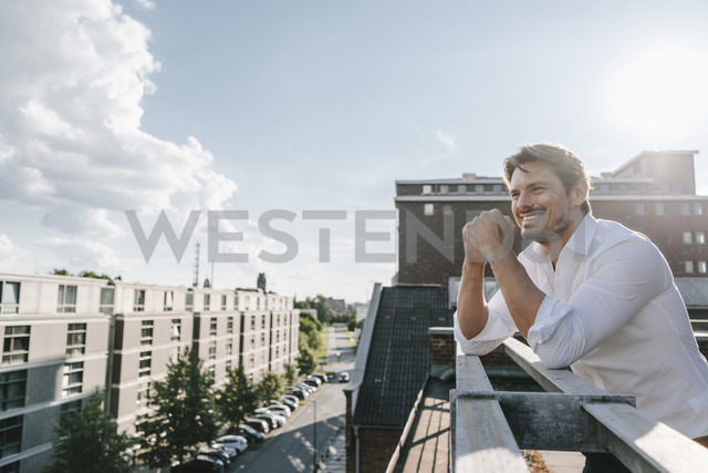 Businessman standing on balcony, smiling - KNSF02858