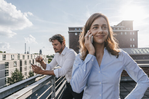 Business people standing on balcony, using smartphone - KNSF02864