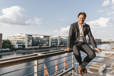 Confident businessman sitting on railing of balcony - KNSF02870