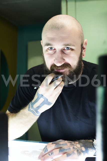 Portrait of tattoo artist designing motif on light table in studio - IGGF00159