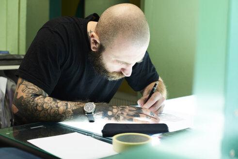 Tattoo artist designing motif on light table in studio - IGGF00162