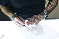 Tattoo artist designing motif on light table in studio - IGGF00165