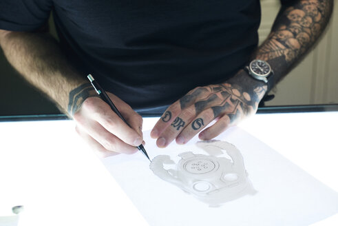 Tattoo artist designing motif on light table in studio - IGGF00165