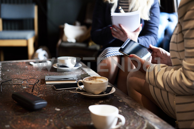 Two businesswomen with tablet and notebook having a meeting at a coffee shop - IGGF00177