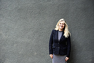 Portrait of smiling senior businesswoman against grey wall - IGGF00183