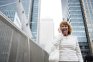 UK, London, smiling senior businesswoman on the phone in the city - IGGF00186