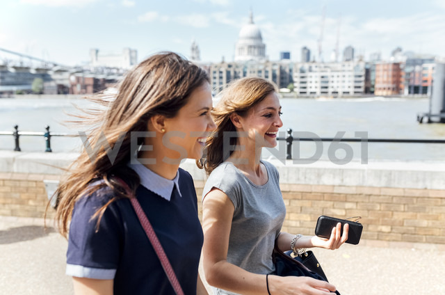 UK, London, two women walking along the banks of the Thames River - MGOF03601