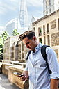 UK, London, man checking his smartphone in the city - MGOF03607