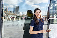 UK, London, portrait of smiling woman with smartphone in the city - MGOF03613