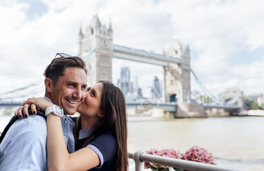 UK, London, happy couple kissing with the Tower Bridge in the background - MGOF03625