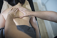Physio massaging woman's back - ZEF14576