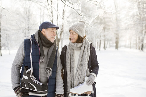 Senior couple with ice skates in winter landscape - HAPF02126
