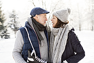 Senior couple with ice skates in winter landscape - HAPF02129