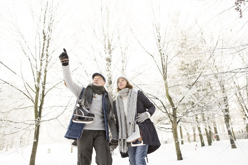 Senior couple with ice skates in winter forest - HAPF02138